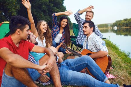 Friends with a guitar on a picnic with a tent on nature in the summer in autumn. Stockfoto