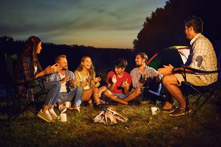 A group of young people are smiling sitting by the fire next to the tent at night in the summer in autumn. Stockfoto