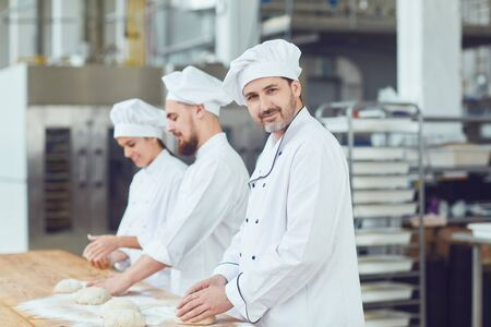 Baker with dough in hand against the background of workers in the bakery. A team of bakers works in the workplace at the bakery.