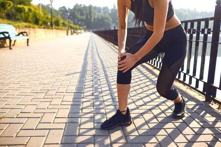 Knee injury in athlete girl in the park. Injury during training. Stockfoto