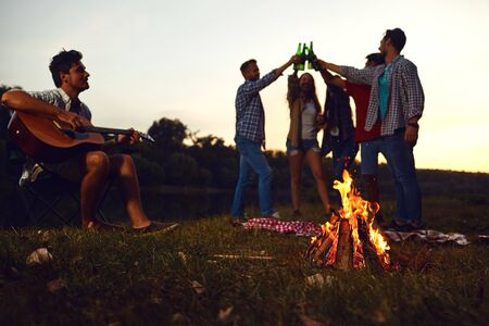 Bonfire at night on a friends picnic in the autumn. Young people clink glasses of bottles on a bonfire background.
