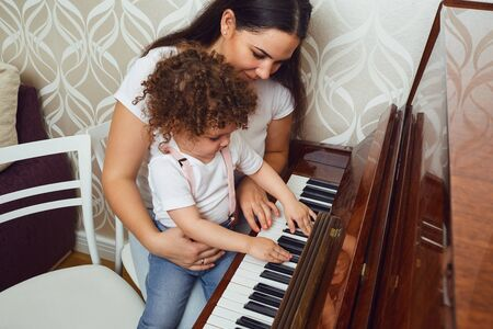Mother teacher teaches the child to play the piano. Piano lesson.