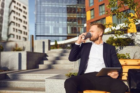 A bearded businessman is drinking coffee while sitting on a city street against the background of a business building.