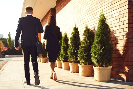 Back view. Business People walk along the city street. Concept success business meeting work professional.