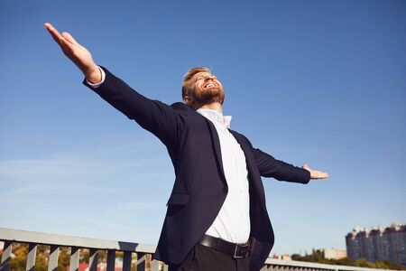 Successful happy businessman on sky background.