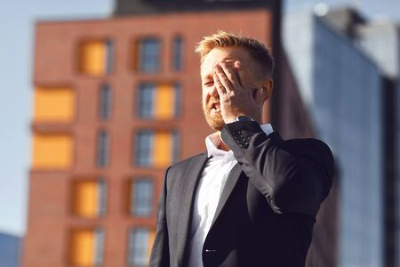 Crisis concept stress problem. Businessman covered his face with his hand on a background of a business building.