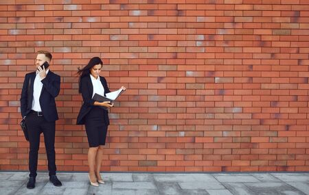 Businesspeople stand on brick wall background. Concept of business job success professional meeting. Stockfoto