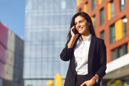 Young Hispanic businesswoman smiling speaks on a mobile outdoors against the background of a business center.