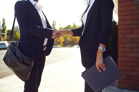 Handshake business. Businessman and business woman make handshakes while standing outdoors at a business building. Success concept deal contract project bank. Stock Photo
