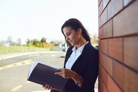 Serious businesswoman is reading documents while standing outdoors.