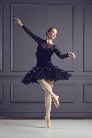 Ballerina ballet dancer in black dress posing over gray background back view. Stockfoto