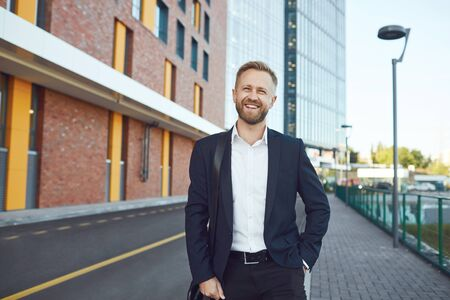 A smiling businessman is standing against the backdrop of a business building on the street. Stockfoto