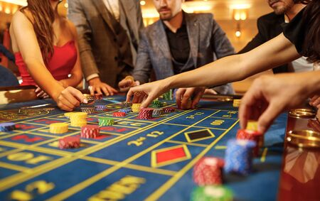 A group of people gamblers playing gambling poker roulette in a casino.