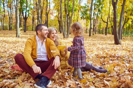 Cheerful family playing with a baby in the park in autumn.