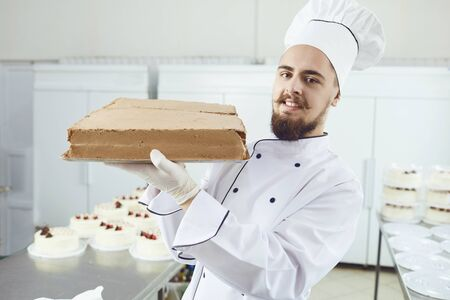 Confectioner smiling man holding cake smiling in a pastry shop