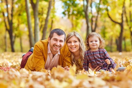 Happy family with a daughter in the park in autumn. Stockfoto