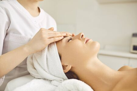 Facial massage for a young woman lying in a beauty salon. Young woman doing facial rejuvenation treatments.