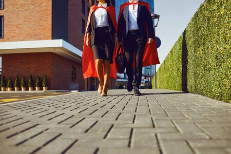 Business people super heroes walk along the city street. Business concept super hero success.
