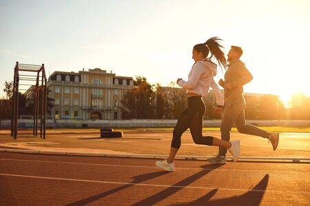 Athletic couple runs in the morning at the stadium. Jogging during training.Jogging. Health. Healthy lifestyle.