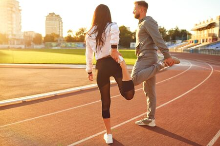 Couple in sportswear doing warm-up at the stadium in the morning in the summer and autumn.