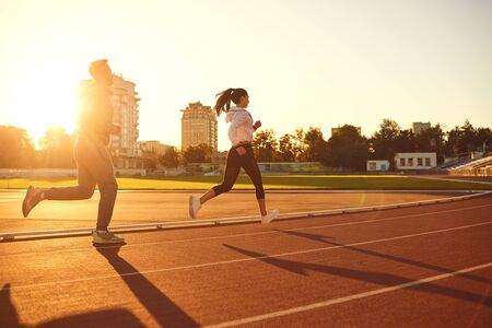 Young man and woman runners run in the morning at dawn.Jogging. Health. Healthy lifestyle. Stockfoto