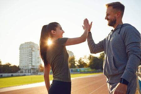 A young couple of athletes raised their hands up in the morning at dawn. Sports people.