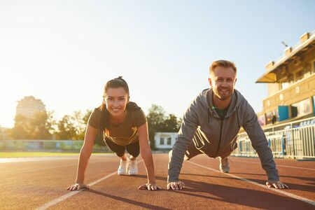 Young couple doing pushups in the stadium in the morning. Sport lifestyle. Stockfoto