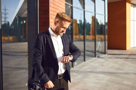 A businessman looks at a wristwatch outdoors. Punctuality. Being late. A man in a suit is waiting for a meeting.