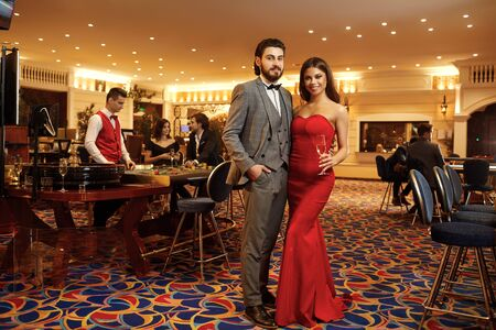 Beautiful glamour couple with glasses of alcohol in hand are standing against the background of casino poker roulette. 版權商用圖片 - 130636440