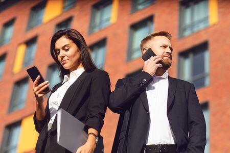 Businessman and businesswoman are talking on the phone while standing outdoors. Business people are talk on a cell phone on the background of a business building. Success concept deal contract project bank.