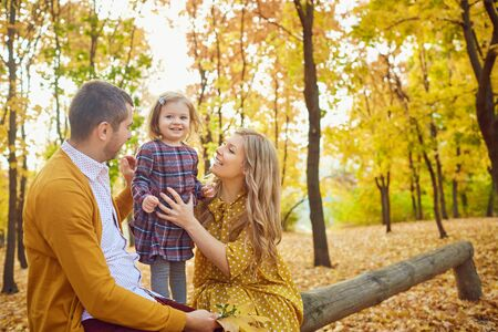 Family smiling while sitting with her daughter in a park in autumn. Stockfoto