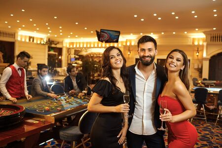 Beautiful glamour people couple smiling are standing against the background of casino poker roulette.