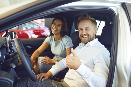 A happy couple bought a new car at a car showroom. Buying and renting cars.