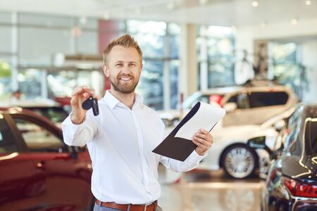 A car dealer smiling standing against the background of cars in a showroom.Buying rental a car. Banco de Imagens