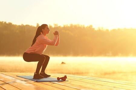 Ein junges Mädchen im Training macht im Sommer im Herbst Kniebeugen bei Sonnenaufgang am See im Park.