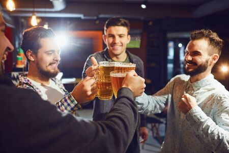 Group of cheerful men smiling and clinking mugs of fresh beer while spending time in modern pub together Banco de Imagens