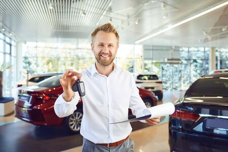A car dealer holds keys in his hand against the background of cars in a showroom.Buying rental a car.