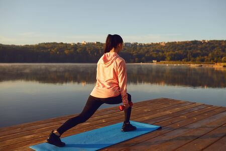 A young girl in training does squats at sunrise by the lake in the park in the summer in autumn.
