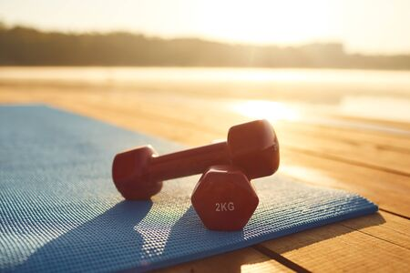 Concept of training fitness exercise workout. Red dumbbells lie on a mat by the lake in a park on nature in the morning at dawn.