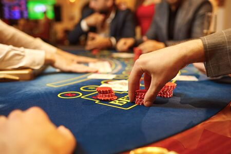 People play poker at the table in the casino. Hands with cards in the hands of a game in a casino.