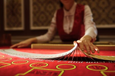 The croupier in the casino does a shuffle of cards at the table. Gambling Banco de Imagens