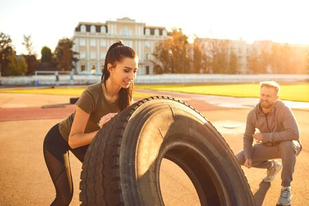 Man and woman doing crossfit outdoors. Athletic girl pushes a tire in the stadium at sunset. Sports people.