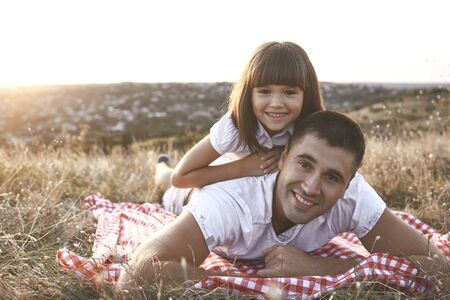 Adult man with little girl on back lying in golden field smiling at camera in sunlight Banco de Imagens