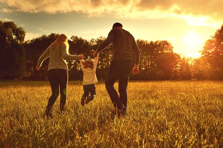 Happy family walks on the park at sunset.Back view. Parents with a child in nature. Children Protection Day.