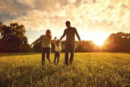 Happy family walks on the park at sunset. Parents with a child in nature. Children Protection Day. Banco de Imagens