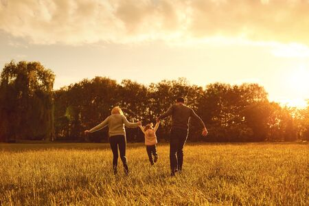Happy family walks on the park at sunset. Parents with a child in nature. Children Protection Day. Banco de Imagens - 131890201