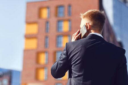Businessman talking on the phone on the background of business building. Banco de Imagens - 131258454