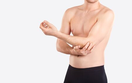 Elbow injury. Pain in the elbow. A man holds an elbow with his hand on a gray background. Stok Fotoğraf