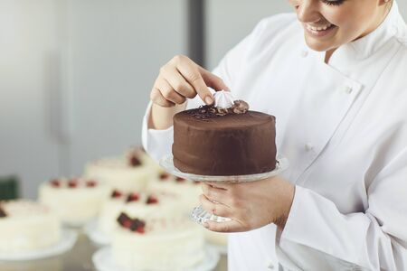 Confectioner woman decorating cake in pastry shop. Imagens