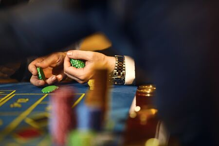Chips in the hands of a player in a casino. Gambling poker roulette in casino.